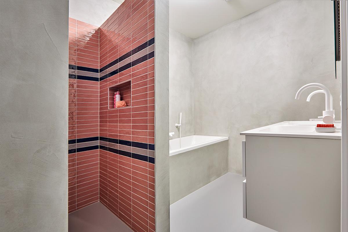 betonlook badkamer met roze tegels